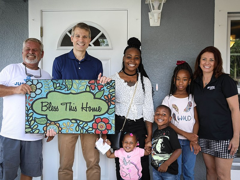 family on front porch of habitat for humanity home in Tampa Bay Florida